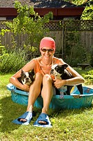 Woman sitting between two Boston Terriers in a wading pool