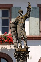 Wine-grower's fountain, statue of a wine-grower with grapes and a grape carrier, Grand'Rue, Ribeauvillé, Alsace, France, Europe