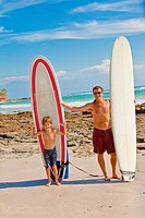 father and son with surfboards in mexico