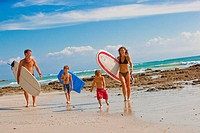 family with surboards on beach in mexico