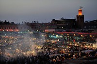 Evening at the Djemaa el Fna market square, literally meaning Assembly of the Dead, with smoke from the many food stalls, behind, the minaret of a mos...