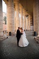 Wedding couple kissing underneath the Colonnade of Saint Peter's square Vatican Rome Italy