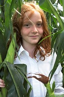 Young girl standing in cornfield