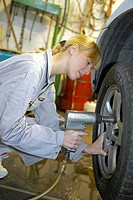 Kfz_Mechanikerin beim Reifenwechsel, female motor mechanic changing car wheel