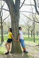 African American couple leaning against tree in park
