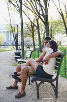 African American couple sitting on bench in park