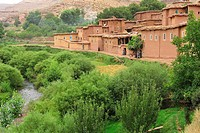 Small Berber village with mud houses on a river with lush vegetation, Kelaa M'gouna, High Atlas, Morocco, Africa