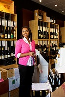 Mixed race small business owner working in wine shop
