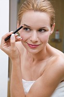 Young pretty woman doing makeup, using eyebrow liner.