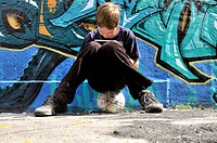 Ten_year_old boy playing with his Nintendo in front of a graffiti wall, Germany, Europe