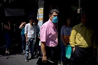 A man wearing a mask as a precaution against swine flu walks in Mexico City's main Zocalo square, April 29, 2009