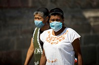 Women wearing masks as a precaution against swine flu walks in Mexico City's main Zocalo square, April 29, 2009