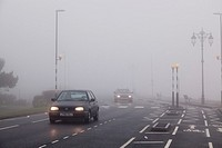 Cars travelling in urban environment with road markings on a foggy day with lights on