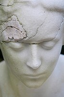 Cracked face of a cemetery statue, portrait, woman