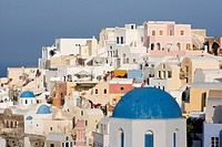 Greece, Santorini, Thira, Oia. Blue dome of Greek Orthodox church with town in the background. Credit: Bill Young / Jaynes Gallery / DanitaDelimont.co...