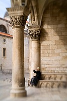 Croatia, Dalmatia, Dubrovnik. Woman photographing square from entrance to Rector´s Palace 15th century. The historic center of Dubrovnik is a UNESCO W...
