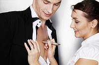 Businesswoman writing on the bare chest of a businessman, symbolic image for love on the job