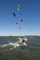 USA, California, Sherman Island. Kiteboarders race in the Sacramento River. Credit: Josh Anon / Jaynes Gallery / DanitaDelimont.com