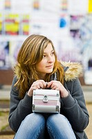 Sitting with a box bag in hand young woman expecting someone