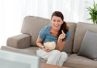Merry woman eating pop corn while watching a movie on television at home