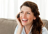 Joyful woman on the phone sitting on the sofa at home