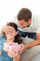 Happy woman receiving a gift from her boyfriend in the living room at home