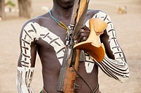 Karo warrior with body paintings, rifle and headrest, Omo river valley, Southern Ethiopia