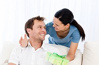 Happy man receiving a present from his girlfriend while sitting on the sofa