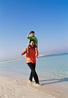 A father carrying his son on his shoulders as he walks barefoot on the seashore.