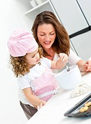 Little girl with her beautiful mother cooking together in the kitchen