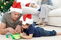 Father and son unwrapping a present lying on the floor in the living room