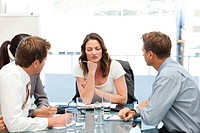 Thoughtful businesswoman at a table with her team during a meeting