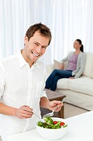 Happy man preparing lunch while his girlfriend relaxing on the sofa