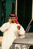 An Arab converses over the cell phone while standing next to his car.