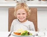 Cute little boy eating pasta and salad in the kitchen