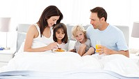 Lovely family having breakfast on the bed at home