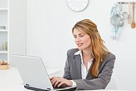 Businesswoman looking at her laptop at home
