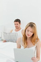 Woman is on her laptop while her husband is reading newspaper in the bed