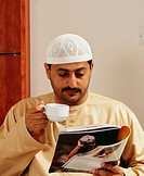 A mature man reads a magazine while having a cup of tea