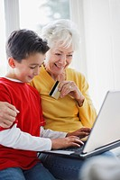 Grandson helping grandmother shop online with credit card