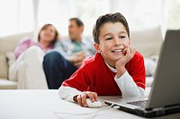 Boy using laptop with parents in background