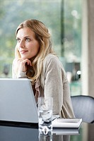 Woman sitting near laptop daydreaming