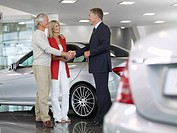 Salesman shaking hands with couple in automobile showroom