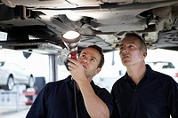 Mechanics looking underneath car in auto repair shop