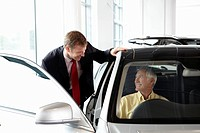 Salesman talking to man in new car in showroom