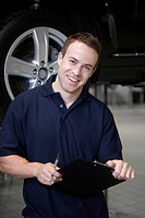 Mechanic with clipboard in auto repair shop