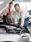 Salesman and customer looking at car engine in automobile showroom