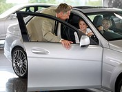 Salesman talking to children in new car in showroom