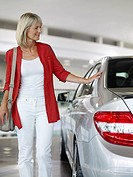 Woman looking at new car in showroom