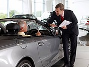 Salesman talking to man in convertible in automobile showroom